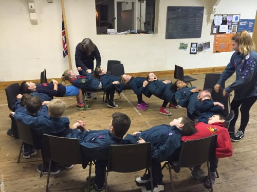 The troop using the chairs in a 'Circle of Trust' exercise